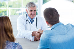 Smiling doctor greeting happy couple. In medical office Stock Image