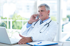 Smiling doctor having phone call at his desk Royalty Free Stock Image