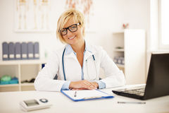 Smiling doctor at her office Royalty Free Stock Photos