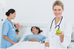 Smiling doctor holding apple with patient in hospital Royalty Free Stock Image