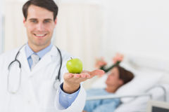 Smiling doctor holding apple with patient in hospital Royalty Free Stock Photo