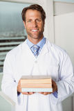 Smiling doctor holding books in medical office Royalty Free Stock Photo