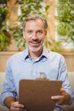 Smiling doctor holding clipboard in clinic Stock Photography