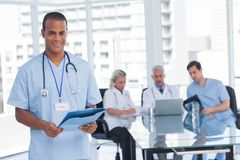 Smiling doctor holding file Royalty Free Stock Image