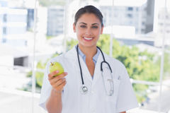 Smiling doctor holding a green apple Royalty Free Stock Images