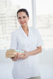 Smiling doctor holding medical books Stock Photo