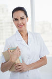Smiling doctor holding medical books Royalty Free Stock Image
