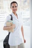 Smiling doctor holding medical books Stock Photos