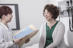 Smiling doctor holding a medical chart and consulting with a patient Stock Photos