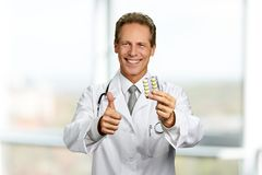 Smiling doctor holding medication. Cheerful medical specialist showing approval sign with finger. New way of treatment stock photos