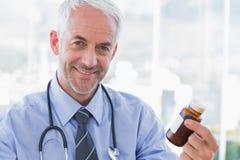 Smiling doctor holding medicine jar Royalty Free Stock Images