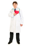 Smiling doctor holding paper heart near chest Stock Photos