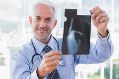 Smiling doctor holding a radiography Stock Photos