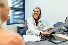 Smiling doctor holding x-ray communicating with patient Royalty Free Stock Images
