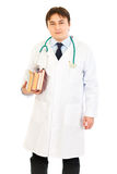 Smiling doctor holding several medical books Stock Image