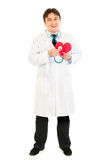 Smiling doctor holding stethoscope on paper heart Stock Image