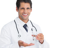 Smiling doctor holding tablets and water Royalty Free Stock Image