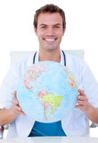 Smiling doctor holding a terrestrial globe Royalty Free Stock Photography