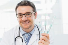 Smiling doctor holding toothbrushes in office Stock Photos