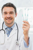 Smiling doctor holding toothbrushes in office Royalty Free Stock Photography