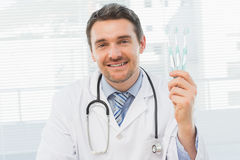 Smiling doctor holding toothbrushes in office Stock Images