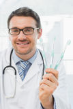 Smiling doctor holding toothbrushes in office Royalty Free Stock Images