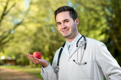 Smiling doctor keeping an apple in hand Royalty Free Stock Images
