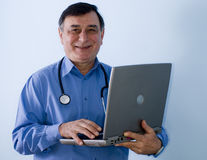 Smiling doctor with laptop. Smiling middle aged doctor with stethoscope around neck and laptop, studio background Stock Image