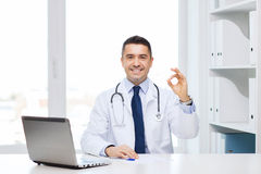 Smiling doctor with laptop showing ok in office Royalty Free Stock Photos