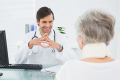 Smiling doctor listening to senior patient at medical office Stock Photo