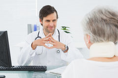 Smiling doctor listening to senior patient at medical office Royalty Free Stock Image