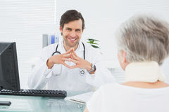 Smiling doctor listening to senior patient at medical office Stock Photography