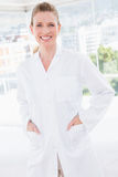 Smiling doctor looking at camera with hands in pockets. In medical office Royalty Free Stock Photos