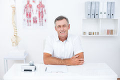 Smiling doctor looking at camera at his desk Royalty Free Stock Photography