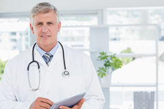 Smiling doctor looking at camera and holding tablet Royalty Free Stock Photos