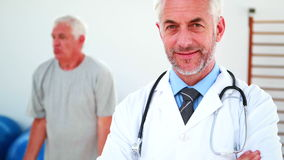 Smiling doctor looking at camera with patient exercising in background