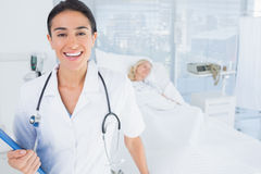 Smiling doctor looking at camera in patients room Royalty Free Stock Photos