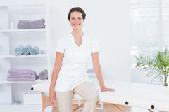 Smiling doctor looking at camera sitting on massage table Royalty Free Stock Images