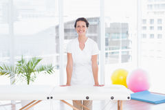 Smiling doctor looking at camera standing behind massage table Royalty Free Stock Images