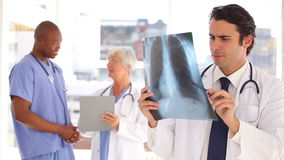 Smiling doctor looking at a chest xray