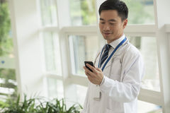 Smiling doctor looking down at his phone in the hospital lobby Royalty Free Stock Image