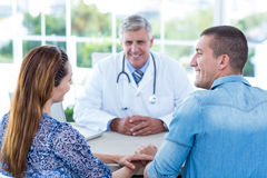 Smiling doctor looking at happy couple royalty free stock photo