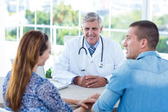 Smiling doctor looking at happy couple Stock Photo