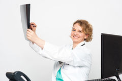 Smiling doctor looking at scanned x-ray report Royalty Free Stock Images