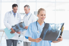 Smiling doctor looking at Xray while her colleagues works Stock Images