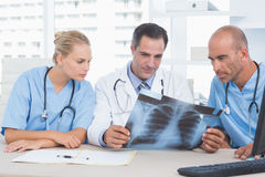 Smiling doctor looking at Xray with his colleagues Royalty Free Stock Photo