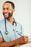 Smiling Doctor or Male Nurse Portrait. Studio shot of a young African American doctor or nurse holding a clipboard Stock Photo