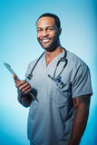 Smiling Doctor or Male Nurse Portrait. Studio shot of a young African American doctor or nurse holding a clipboard Stock Images