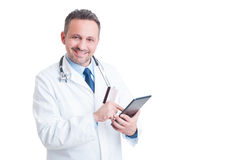Smiling doctor or medic using credit  card and wireless tablet Stock Images