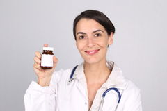 Smiling doctor or nurse holding up tablets Stock Photo